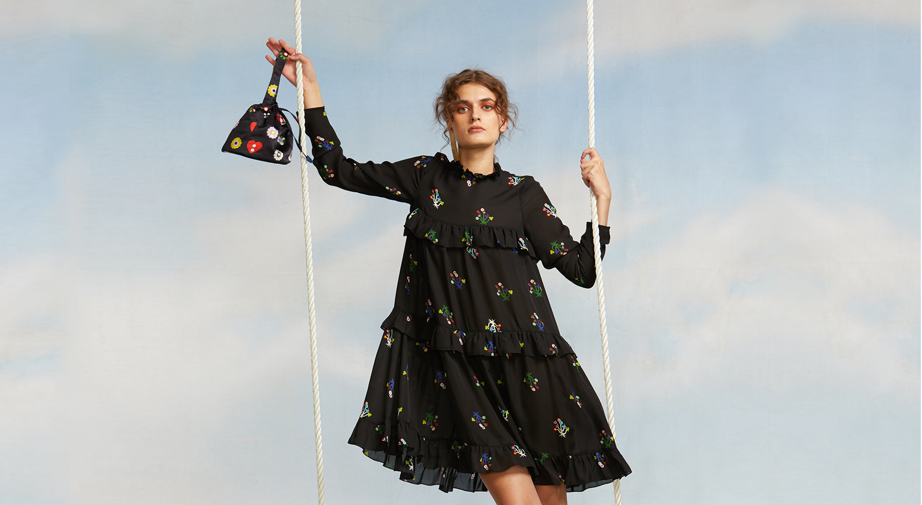 Image featuring a model swinging on a blue sky with clouds background wearing a tiered long sleeve knee length dress in a dar mini floral print.