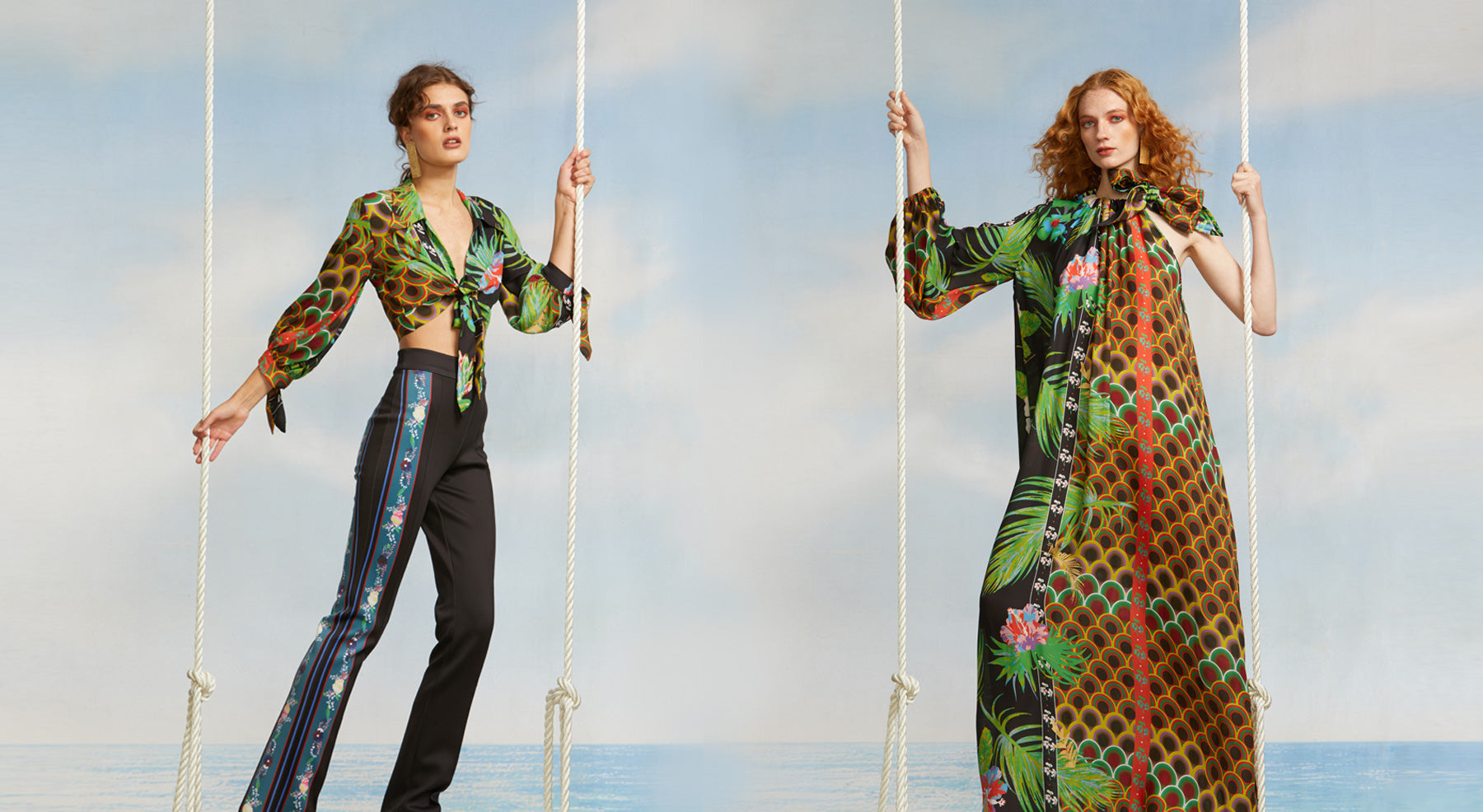 Models on swings wearing a silk top in jungle sunset print and bonded printed flares and a one sleeve maxi dress in jungle sunset print silk.