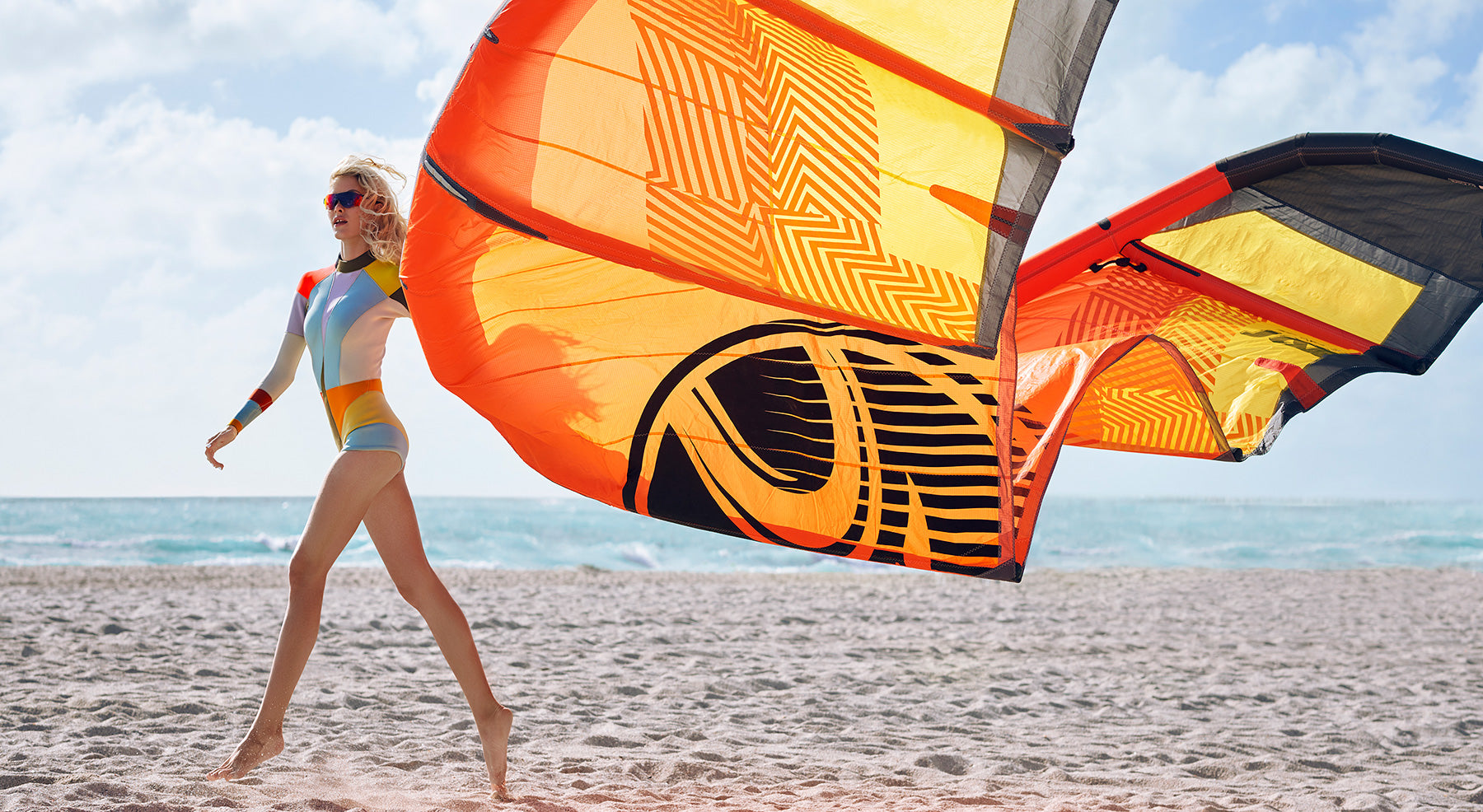 Model on a beach flying a kite wearing a multi color neoprene colorblock wetsuit