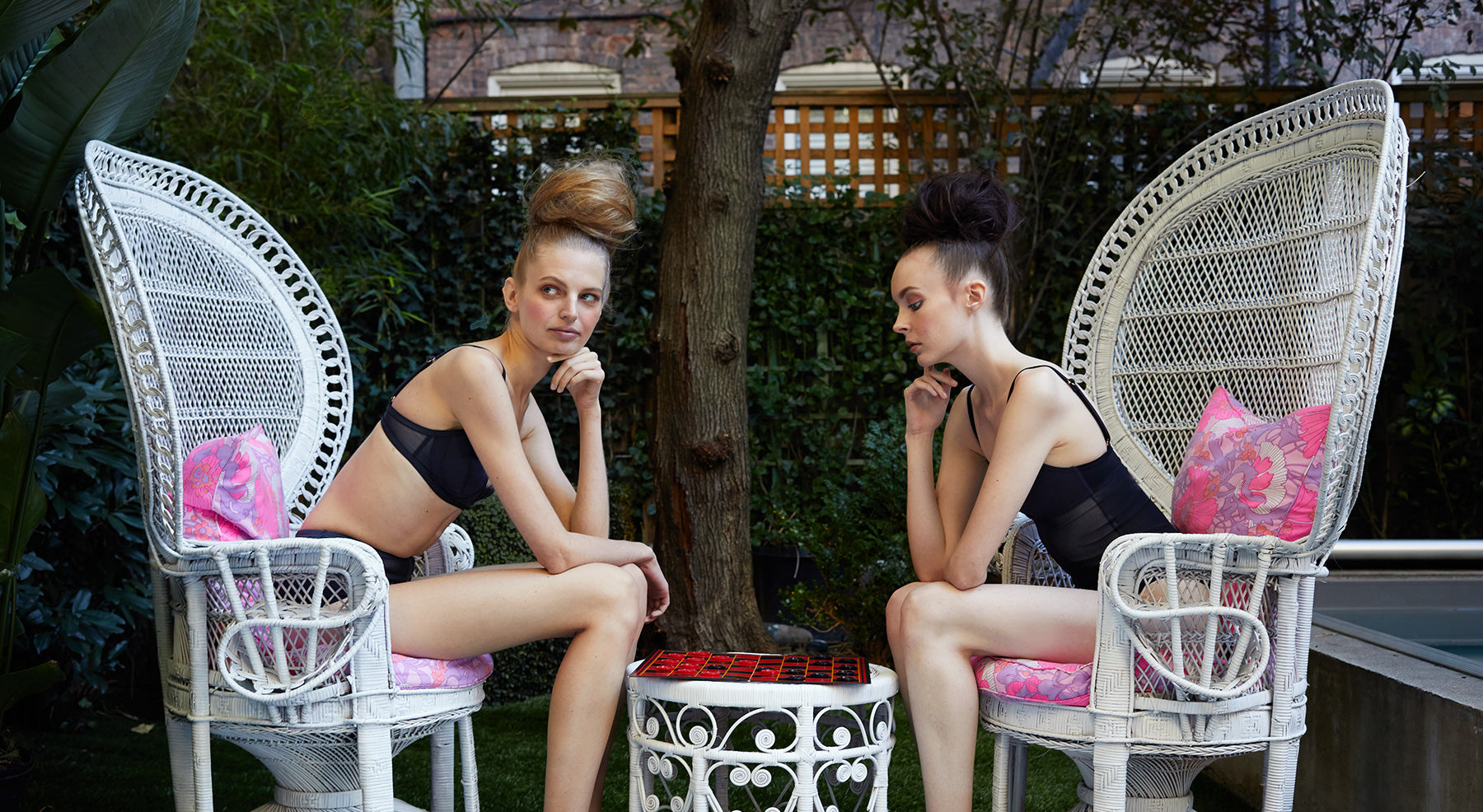 Lifestyle image of models playing checkers featuring the Lola bikini and one piece swimsuits with sheer mesh inserts.