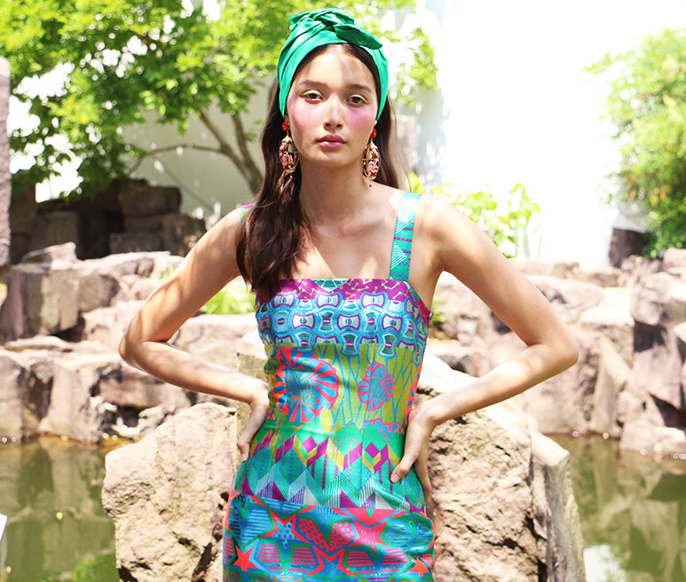 Lifestyle image featuring the Monte Carlo brocade mini dress in a garden setting.
