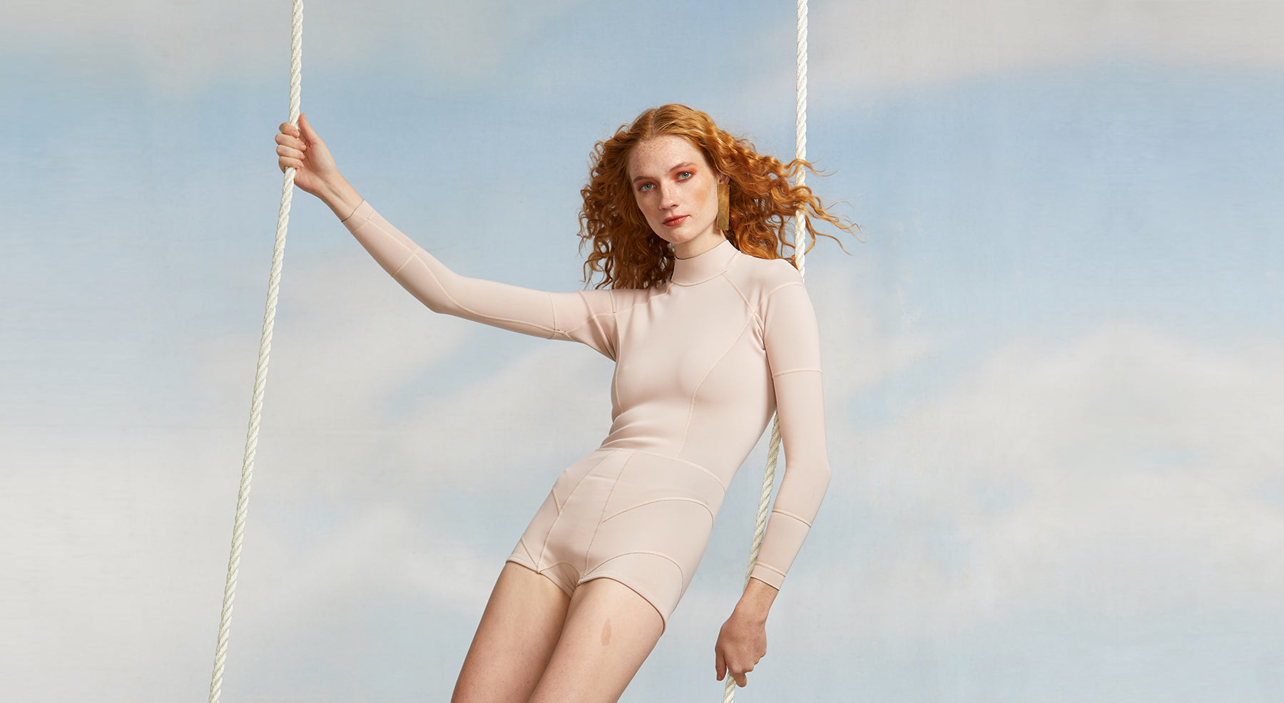 Image featuring a model swinging on a blue sky with clouds backdrop wearing a light pink neoprene wetsuit.