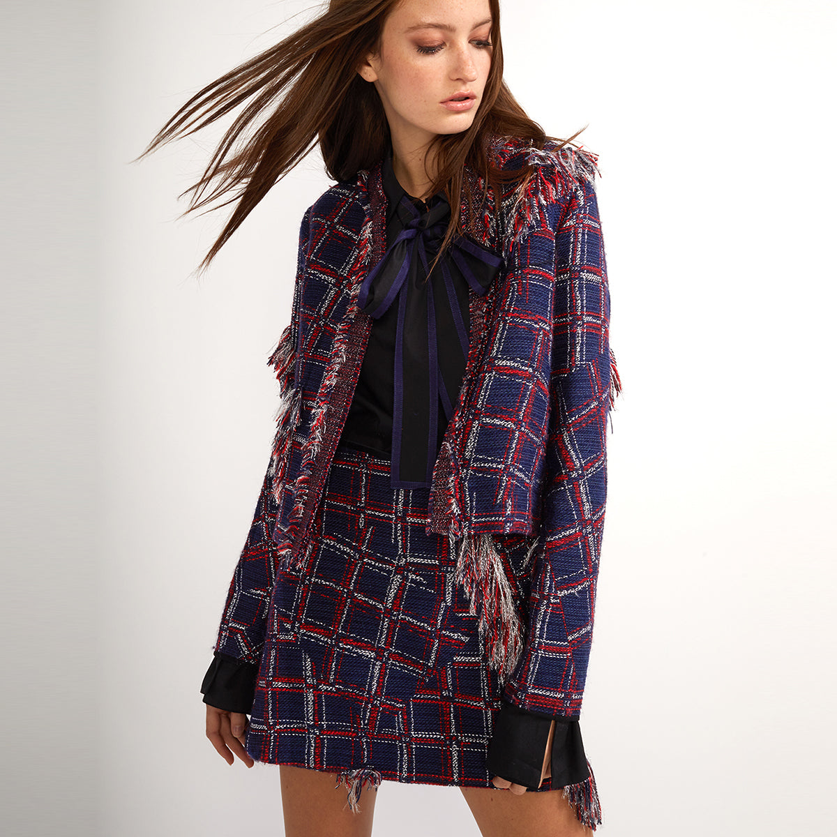 Model wearing a plaid fringe tweed jacket and mini skirt