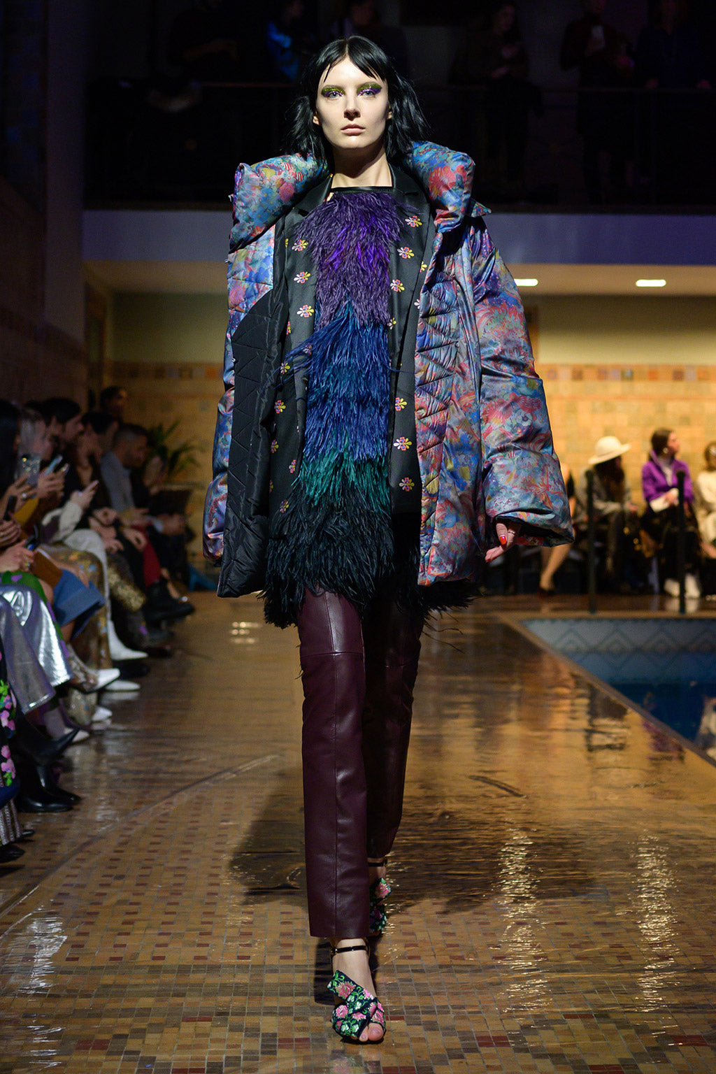 Cynthia Rowley Fall 2019 look 5 featuring a mini dress with multi-colored feathers, wine red leather pants, and puffer jacket with multi-color print