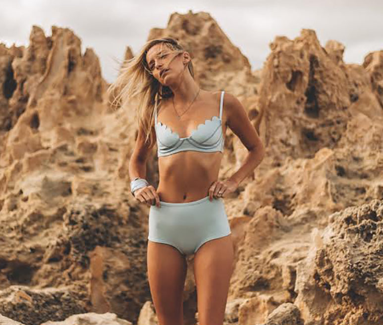 Lifestyle image of girl in rocky coral wearing the light blue neoprene Betty bikini