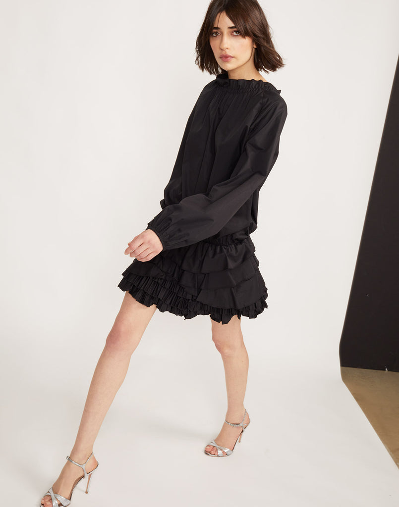 Model walking in the Lenox pleated ruffle mini dress in black polished cotton.