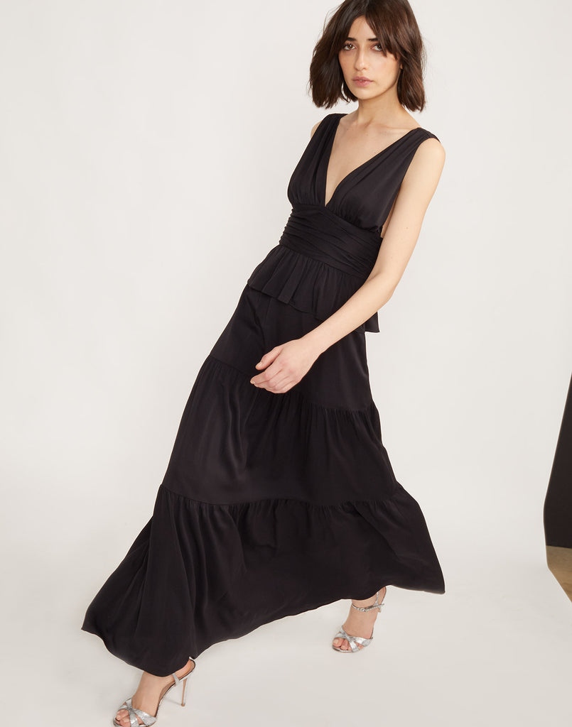 Full partial side walking view of model wearing Zadie tiered maxi dress in black.