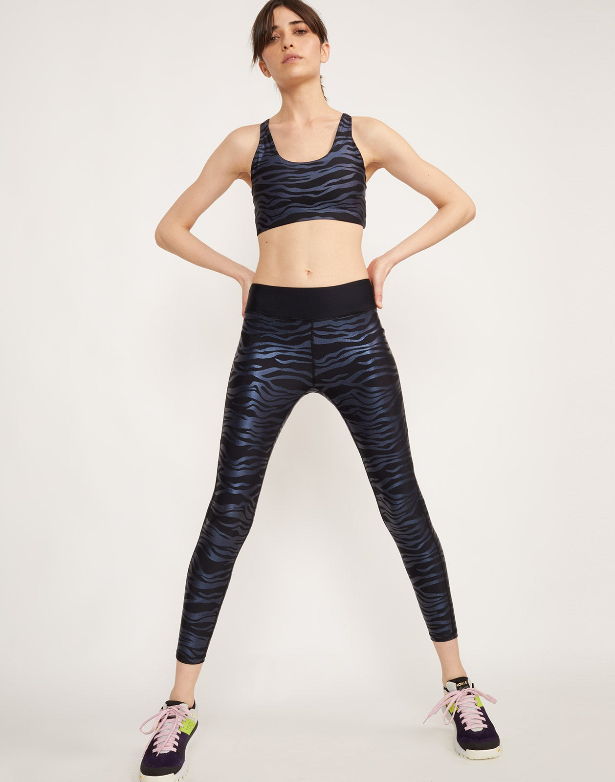 Full view of model wearing Zebra Larkin Sports Bra in navy and black zebra print with Zebra Lincoln legging.