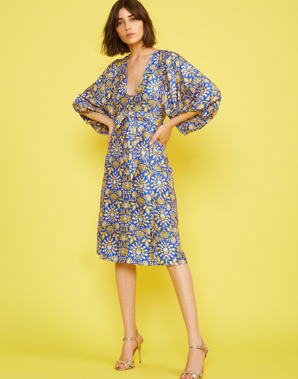 Angled front view of the Daley Waist Tie Dress with silk floral print and voluminous sleeves and waist tie