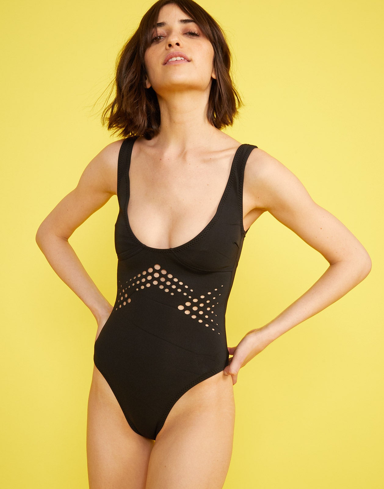 Front full view of model wearing Maui perforated one piece in black.