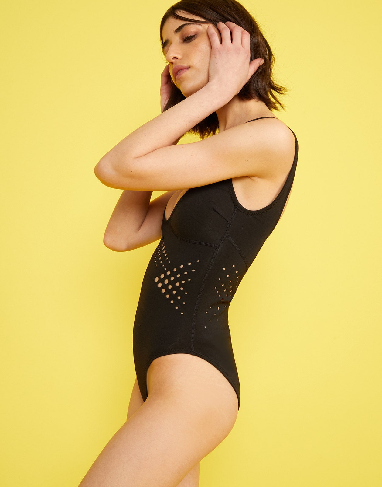 Side full view of model wearing Maui perforated one piece in black.