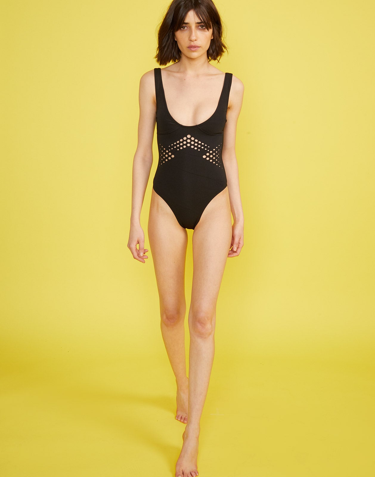 Full length view of model wearing Maui perforated one piece in black.