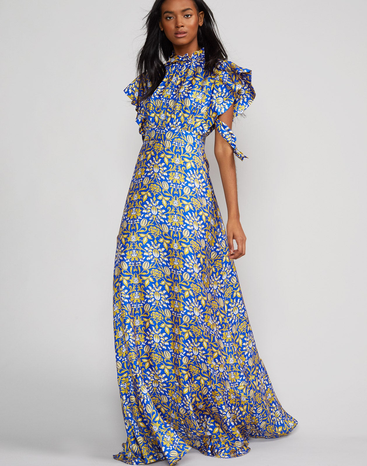 Full length view of model wearing Talia flutter sleeve silk floral print maxi dress in royal print.