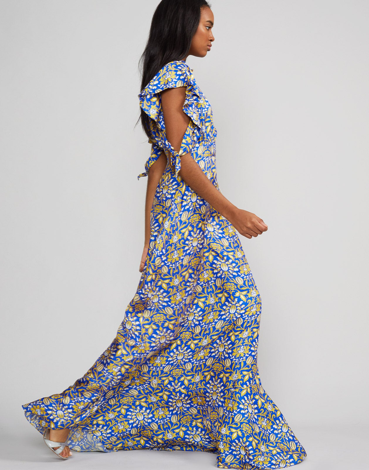 Full length side view of model wearing Talia flutter sleeve silk floral print maxi dress in royal print.