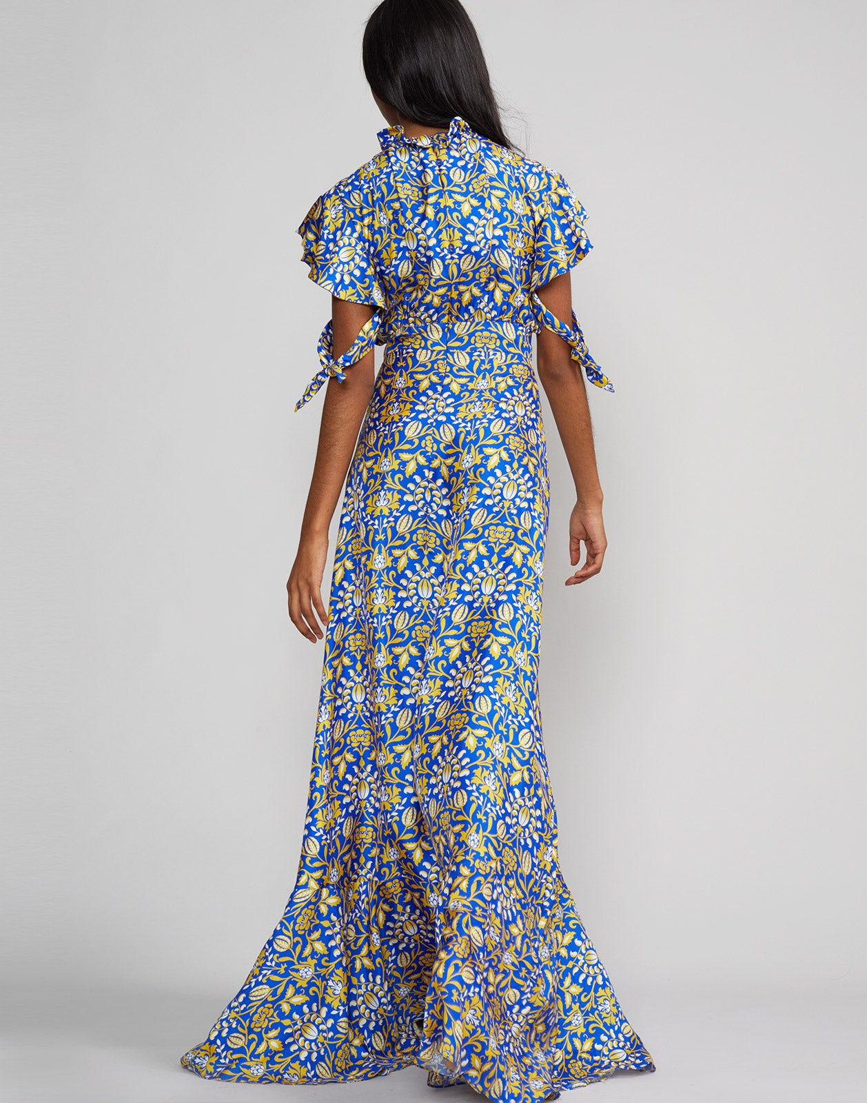 Full length back view of model wearing Talia flutter sleeve silk floral print maxi dress in royal print.