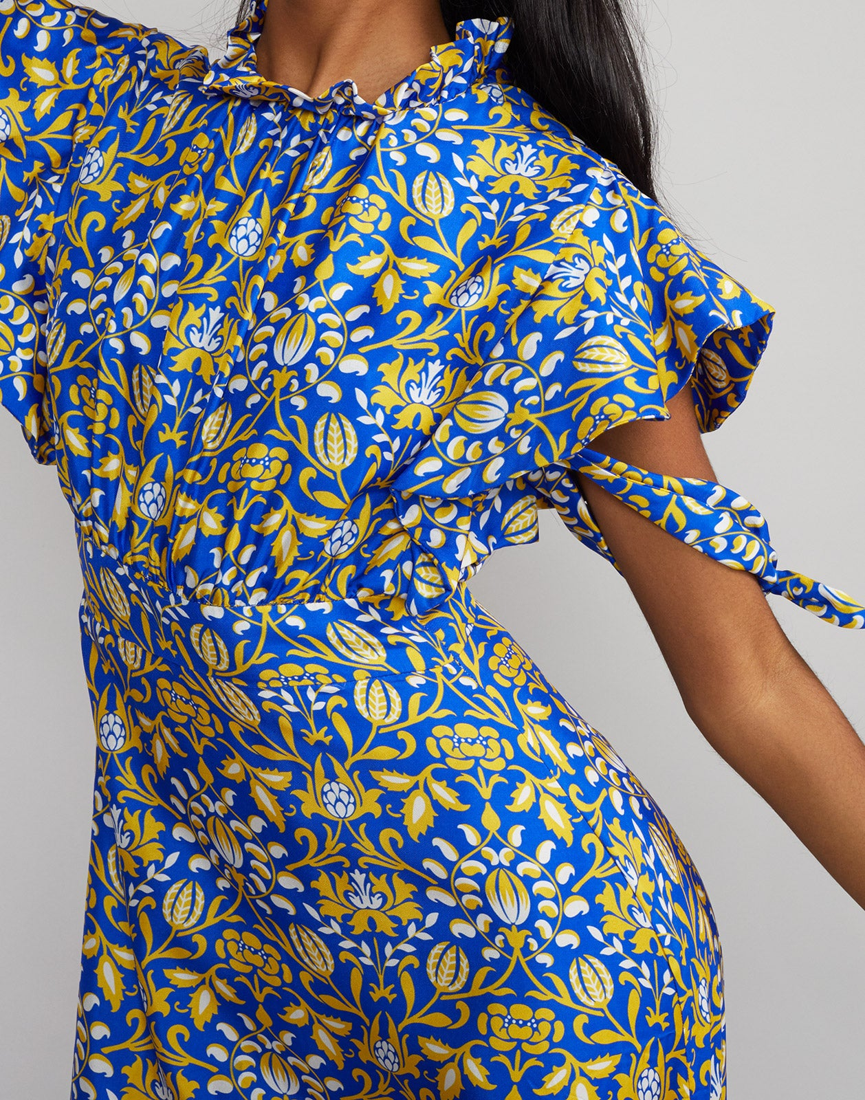 Close up view of model wearing Talia flutter sleeve silk floral print maxi dress in royal print.