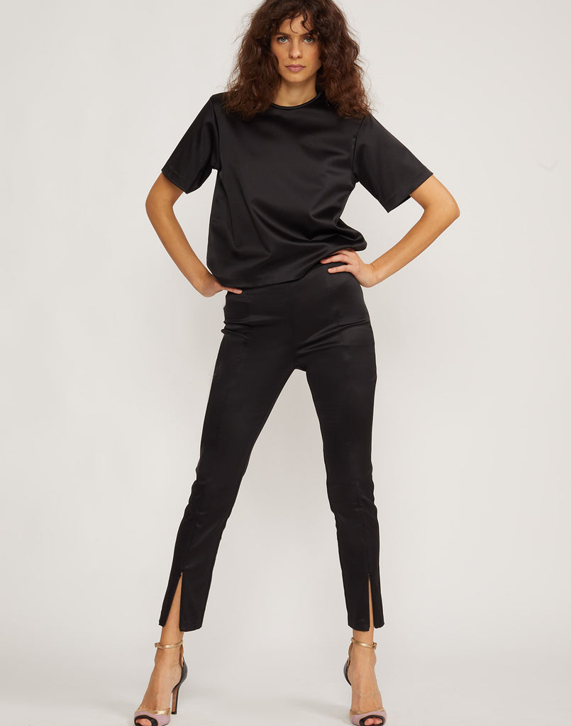 Front view of model wearing black Rush stretch satin pant.