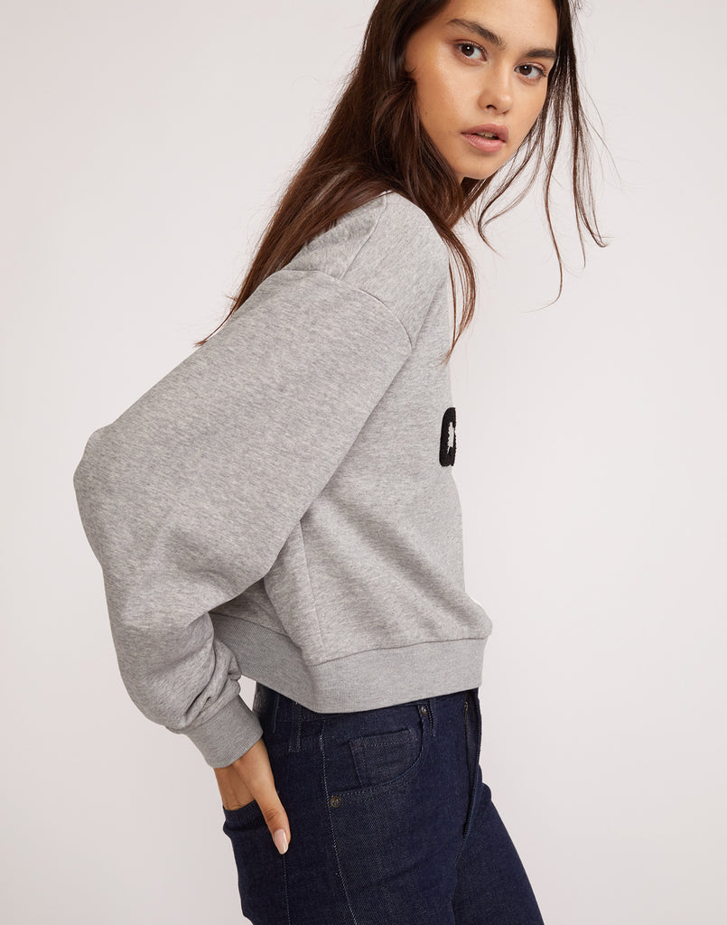 Close side view of the grey and white cropped CaliYork sweatshirt.