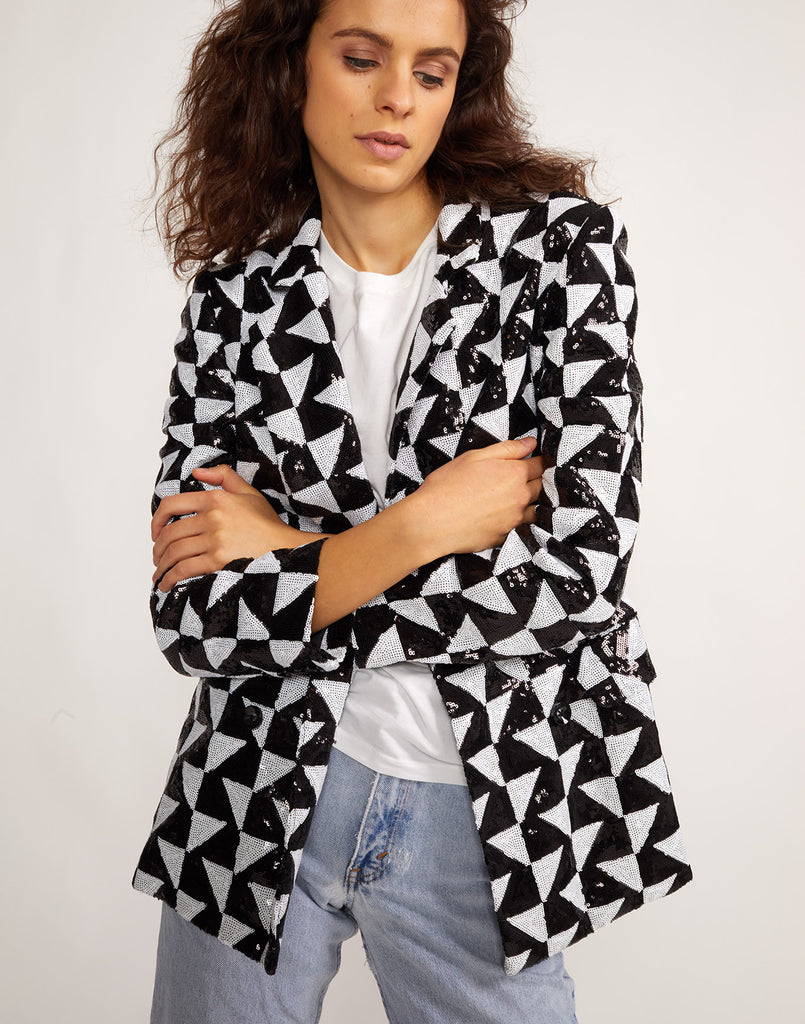 Front view with arms crossed of the Illusion black and white geometric sequin blazer.