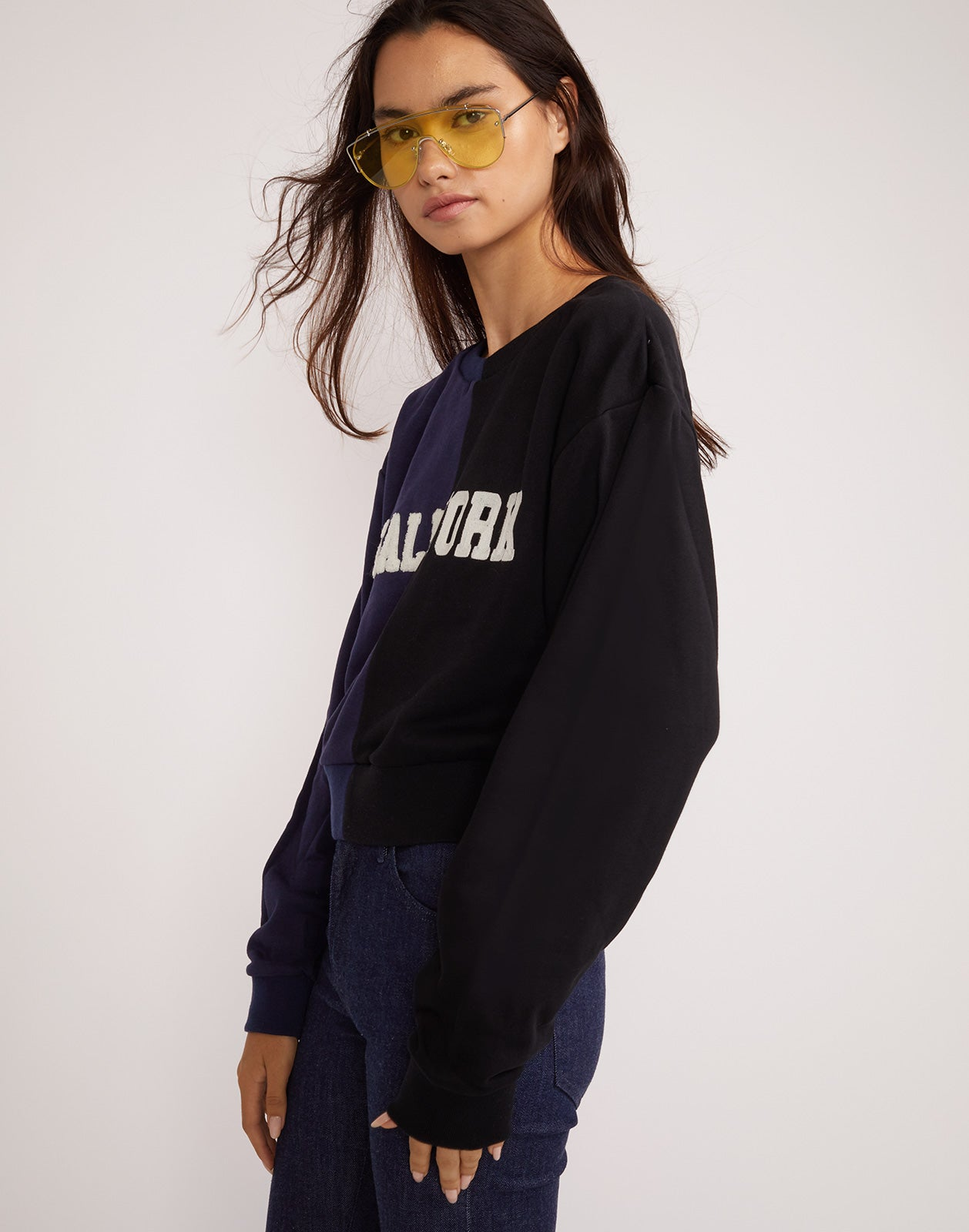 Side view of the CaliYork cropped sweatshirt in half navy half black.