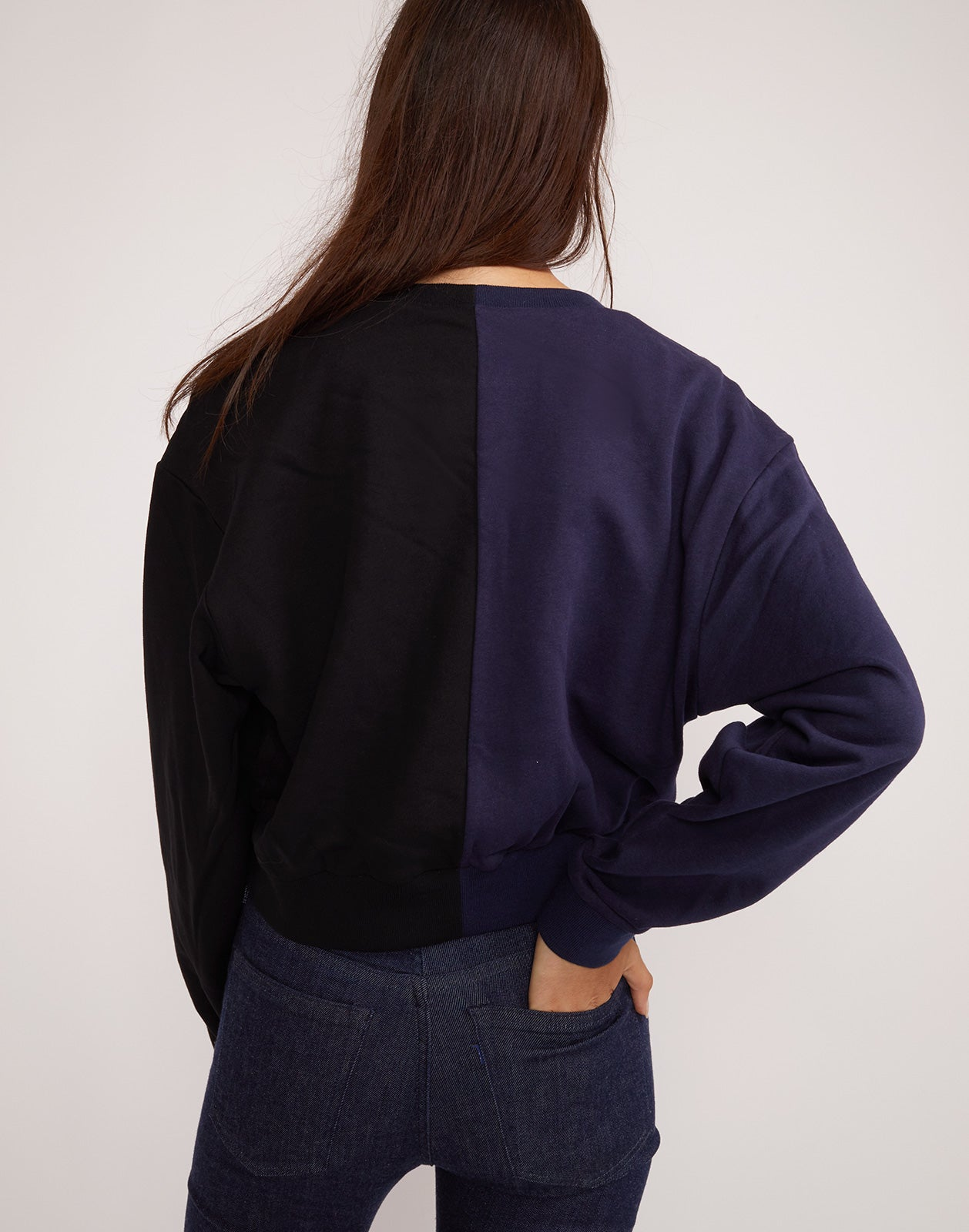 Back view of the CaliYork cropped sweatshirt in half navy half black.