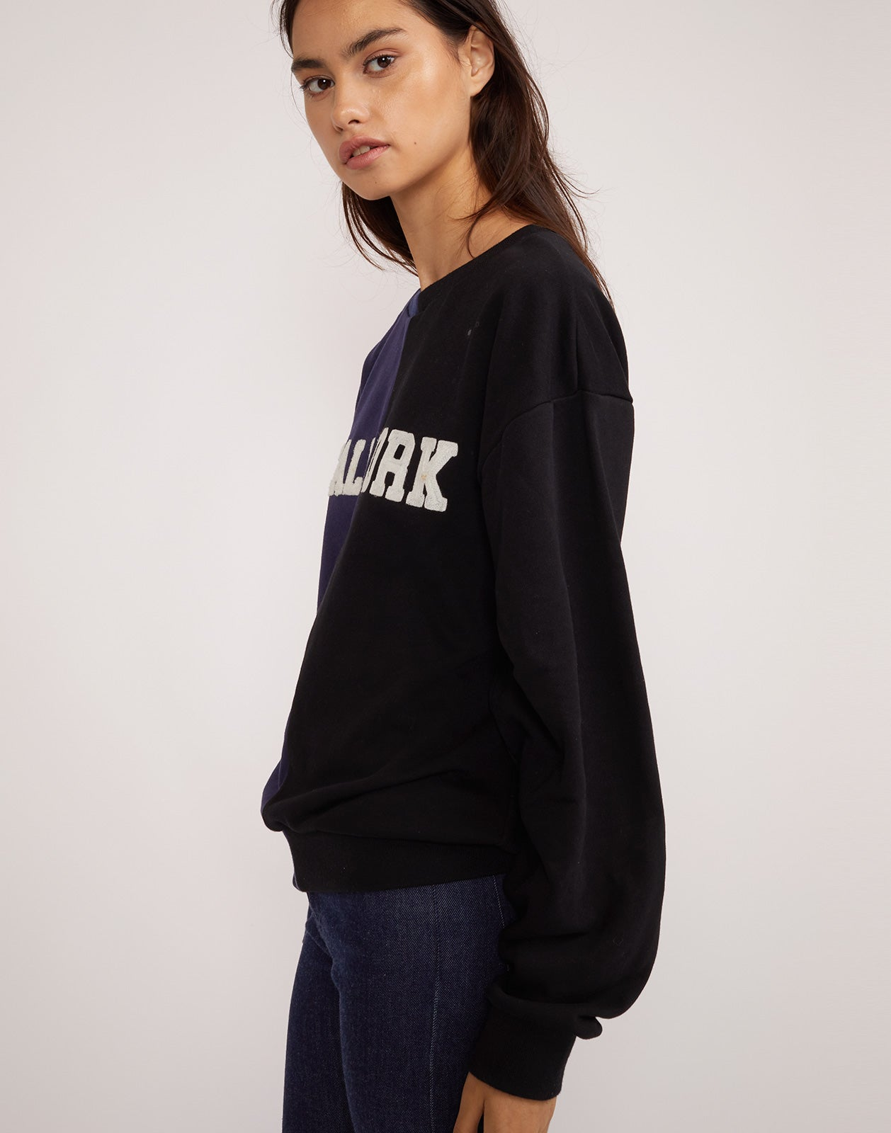 Side view of the CaliYork sweatshirt in half navy half black.