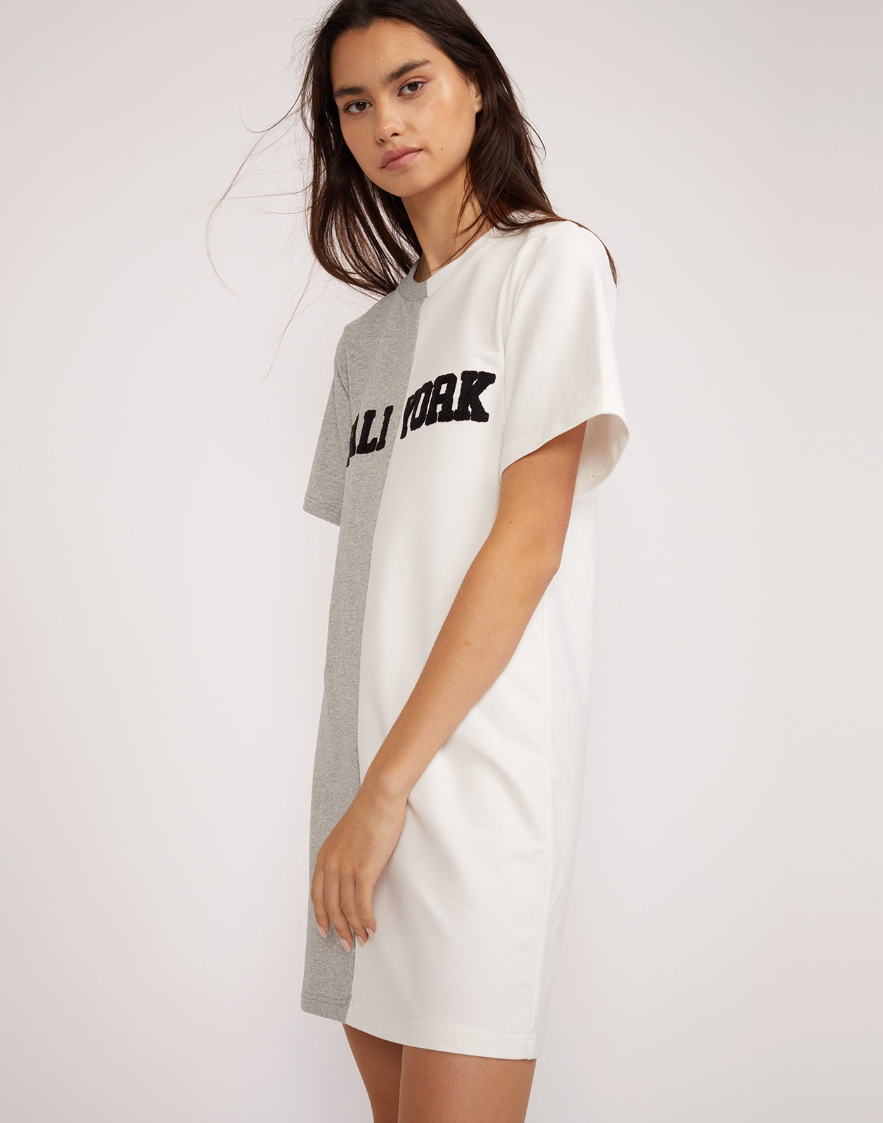 Side view of the CaliYork t-shirt dress in half grey half white with black lettering.