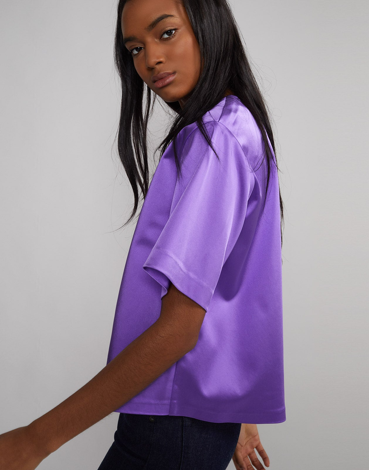 Side view of model wearing Rush Stretch Satin T-Shirt in ultraviolet.