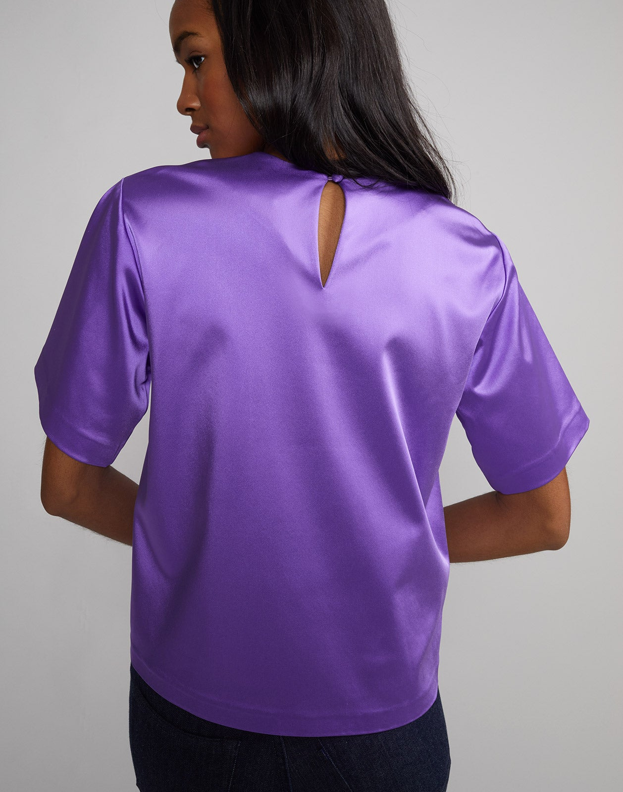 Back view of model wearing Rush Stretch Satin Tee in ultraviolet.