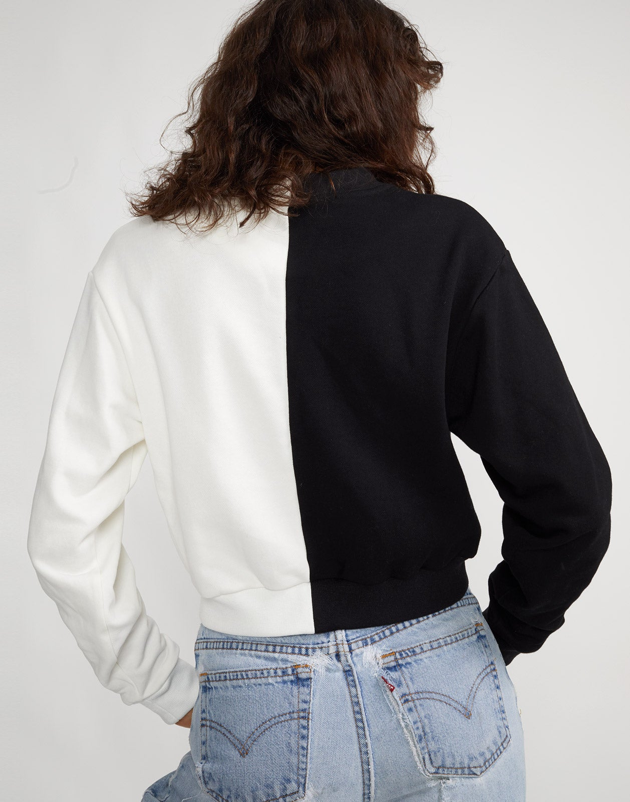 Back view of the CaliYork sweatshirt in half black, half white with hot pink lettering.