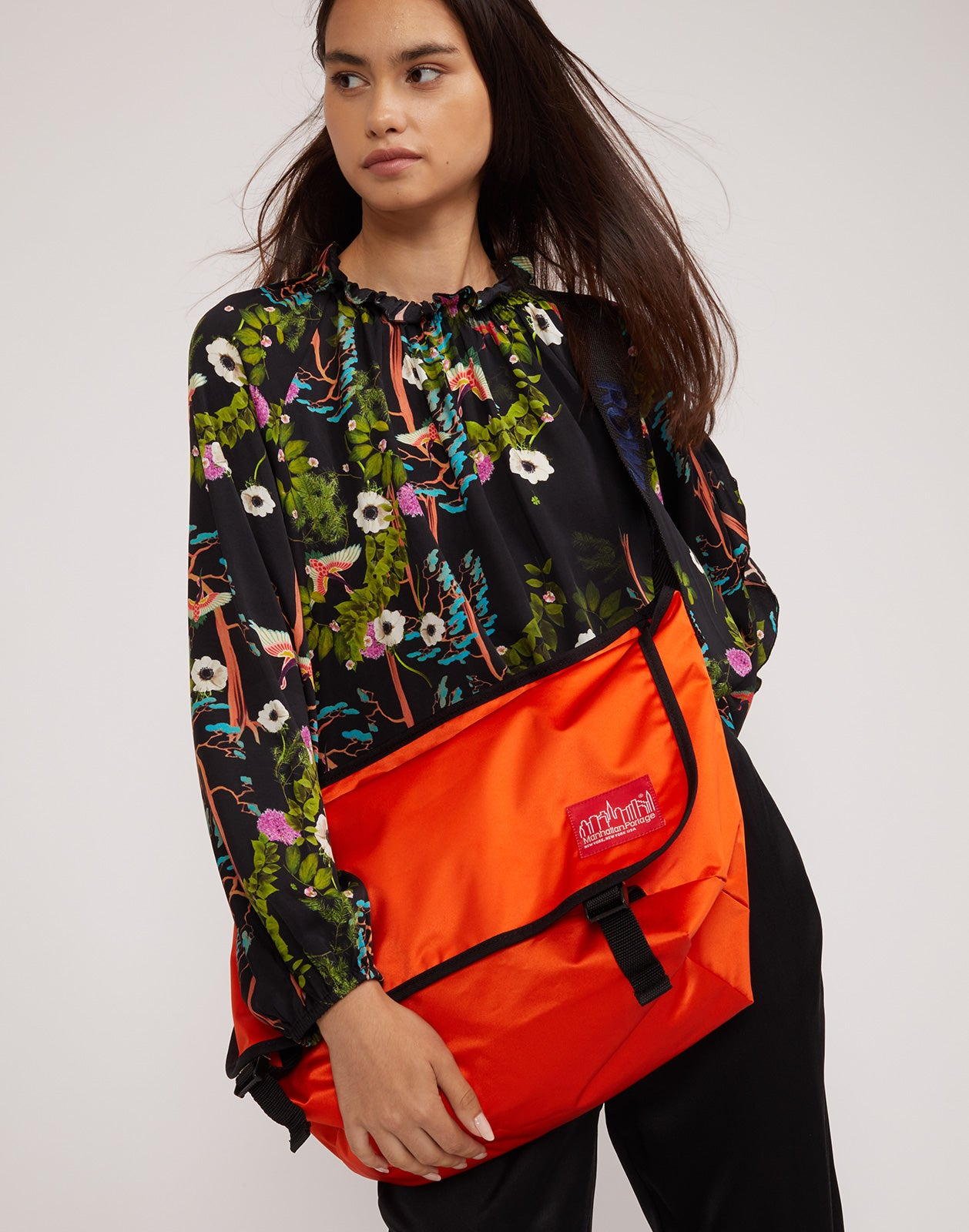 ROWLEY x Manhattan Portage messenger bag in bold orange worn crossbody over the Windsor dark floral blouse.