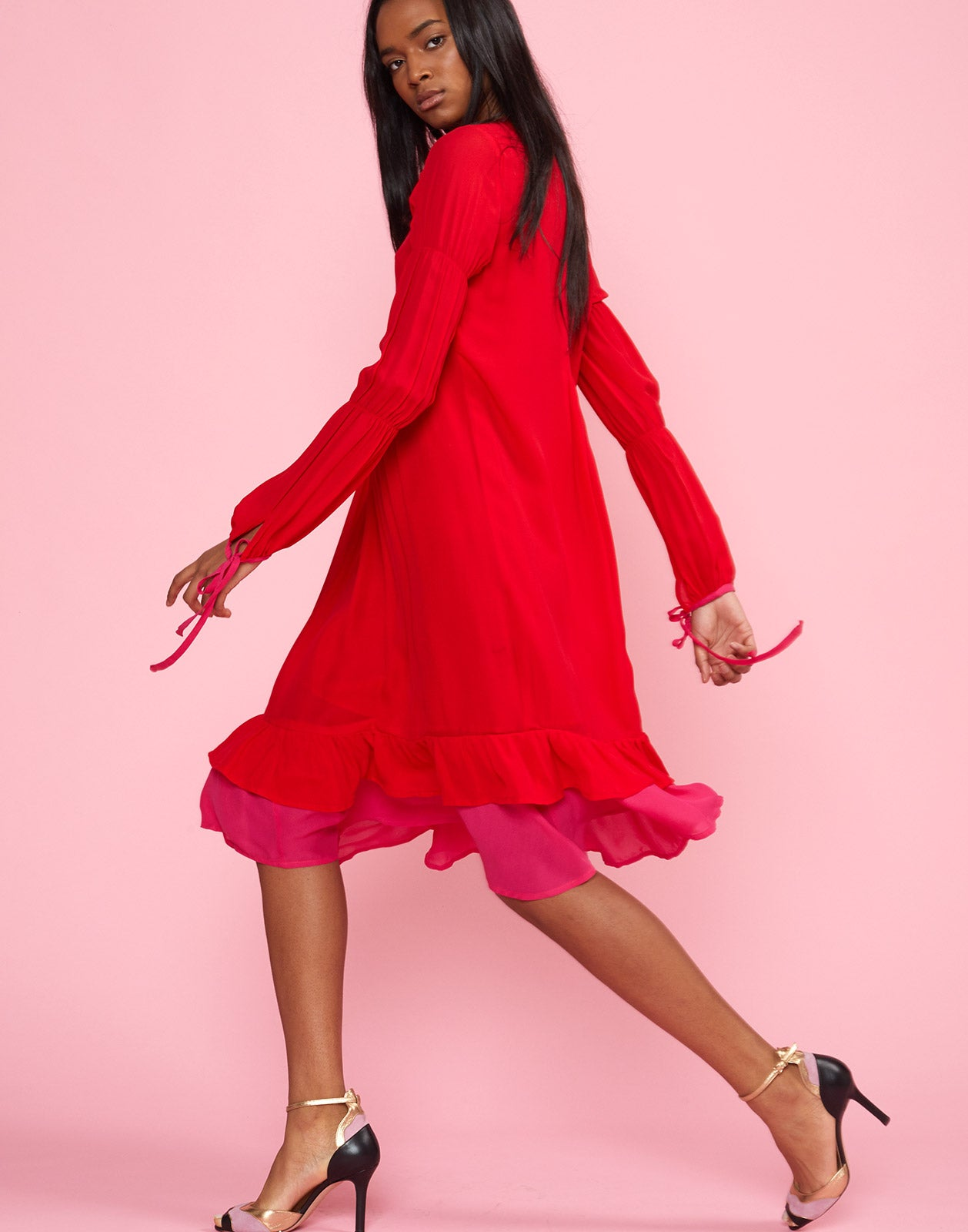 Full side view of model wearing Isla Pinktuck Dress in cherry red.