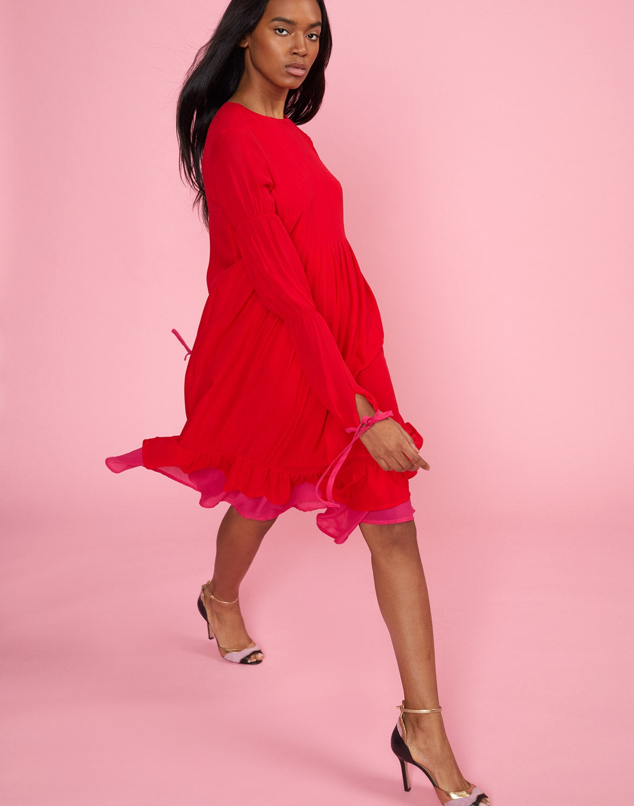 Full side view of model walking wearing Isla Pinktuck Dress in cherry red.