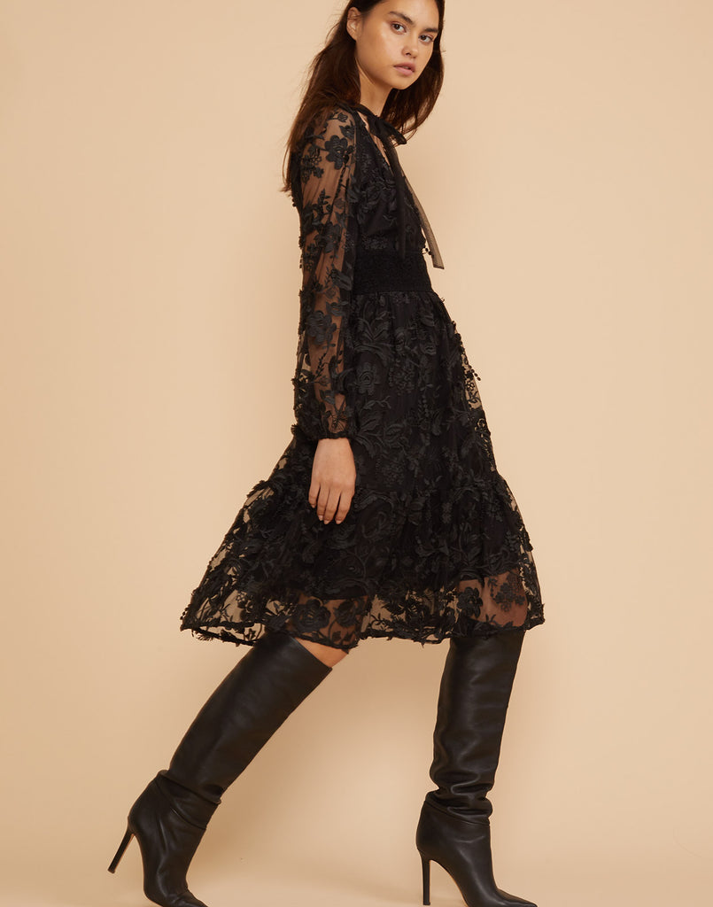 Side view of model walking in the Harlow black lace dress with long sleeves.