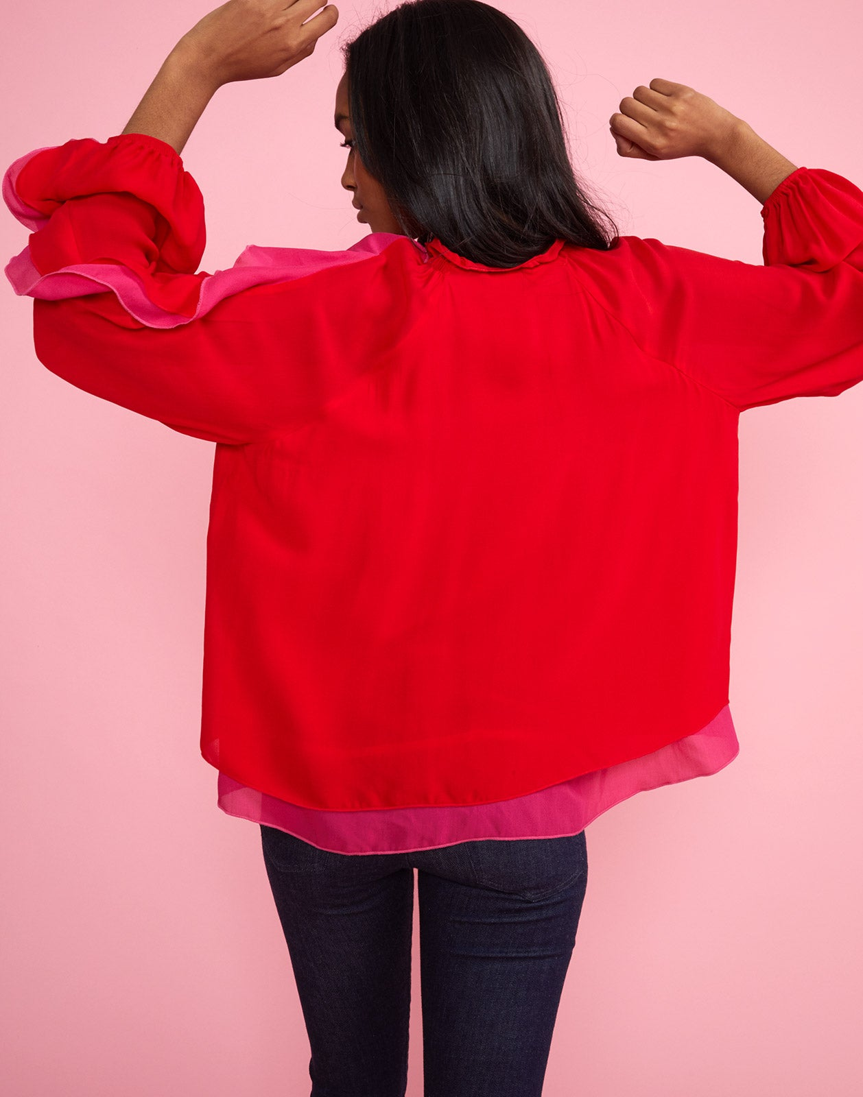 Back view of model wearing High Tide smocked ruffle neck blouse.