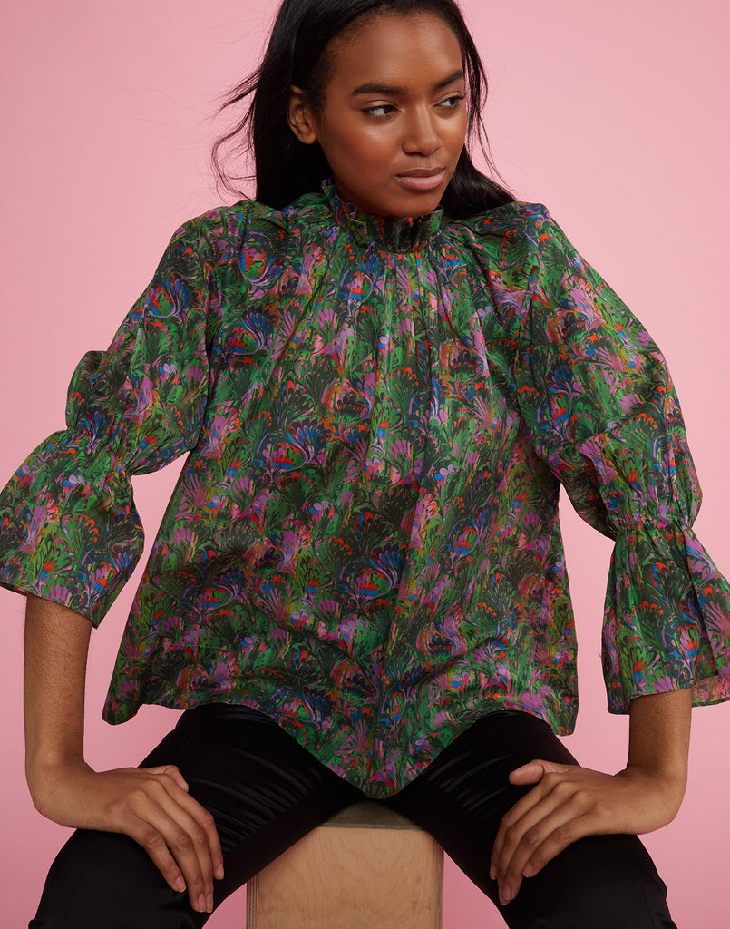 Front seated view of model wearing Marble Cotton Waterfall Blouse.