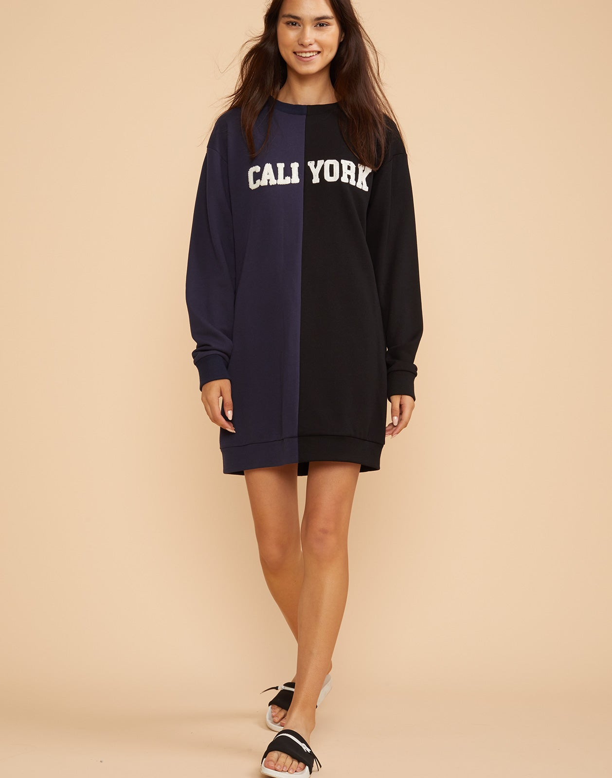 Front view of the CaliYork sweatshirt dress in half navy half black.