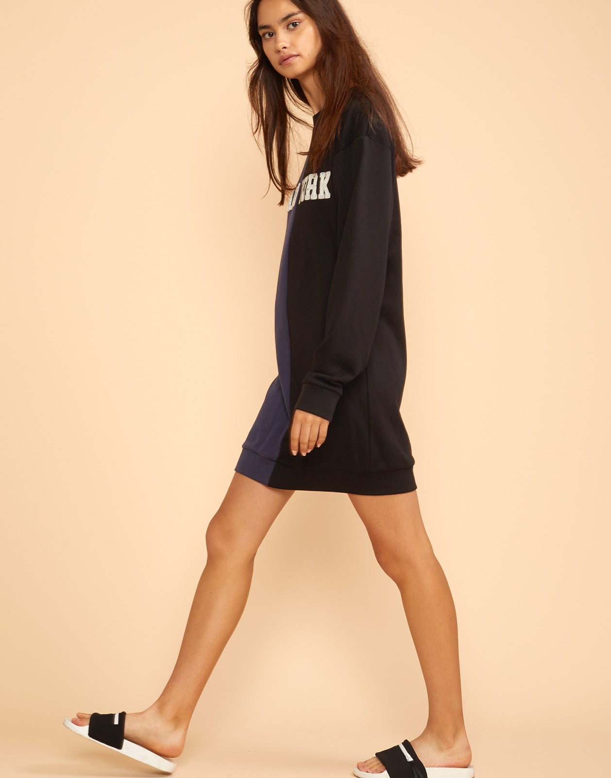 Side view of the Caliyork sweatshirt dress in half navy half black.