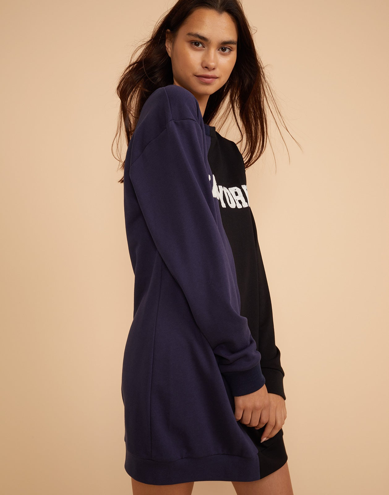 Close side view of the CaliYork sweatshirt dress in half navy half black.