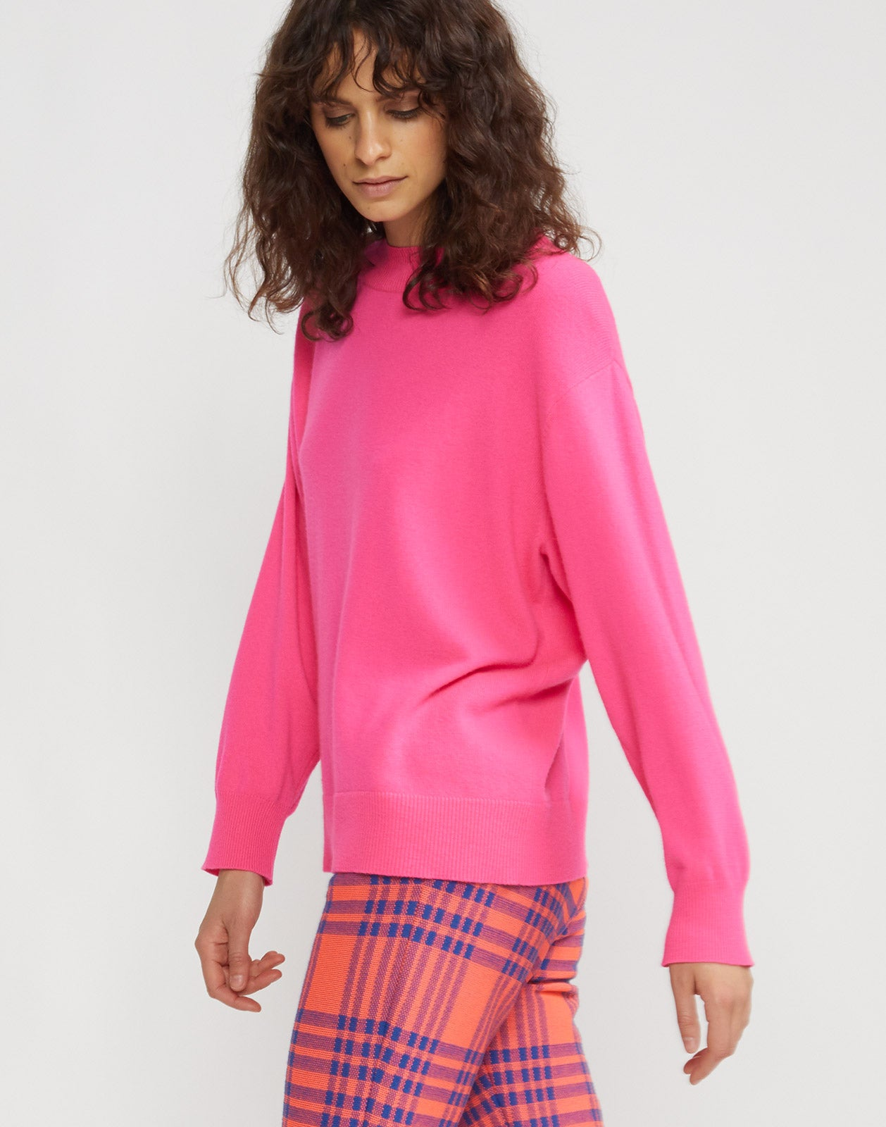Side view of model wearing Anna cashmere sweater in fuchsia.
