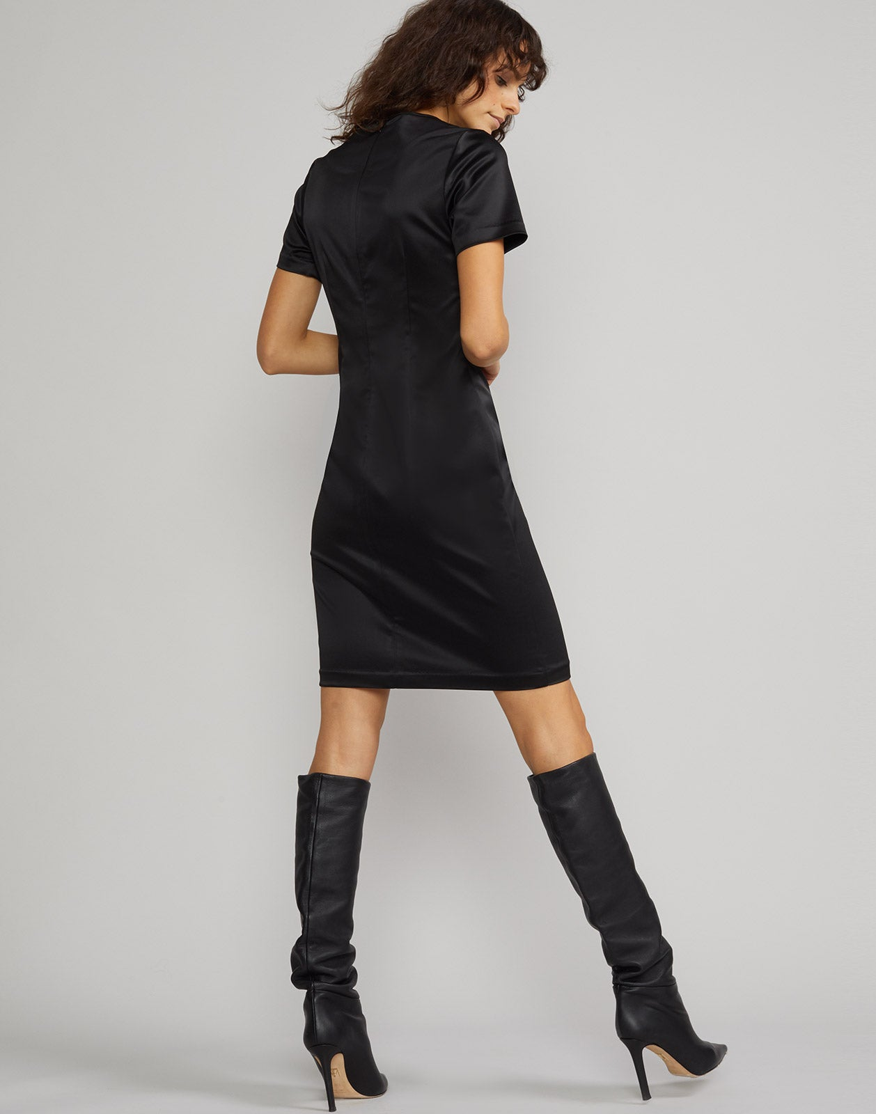 Back view of model wearing Lake Shore stretch satin t-shirt dress in black.