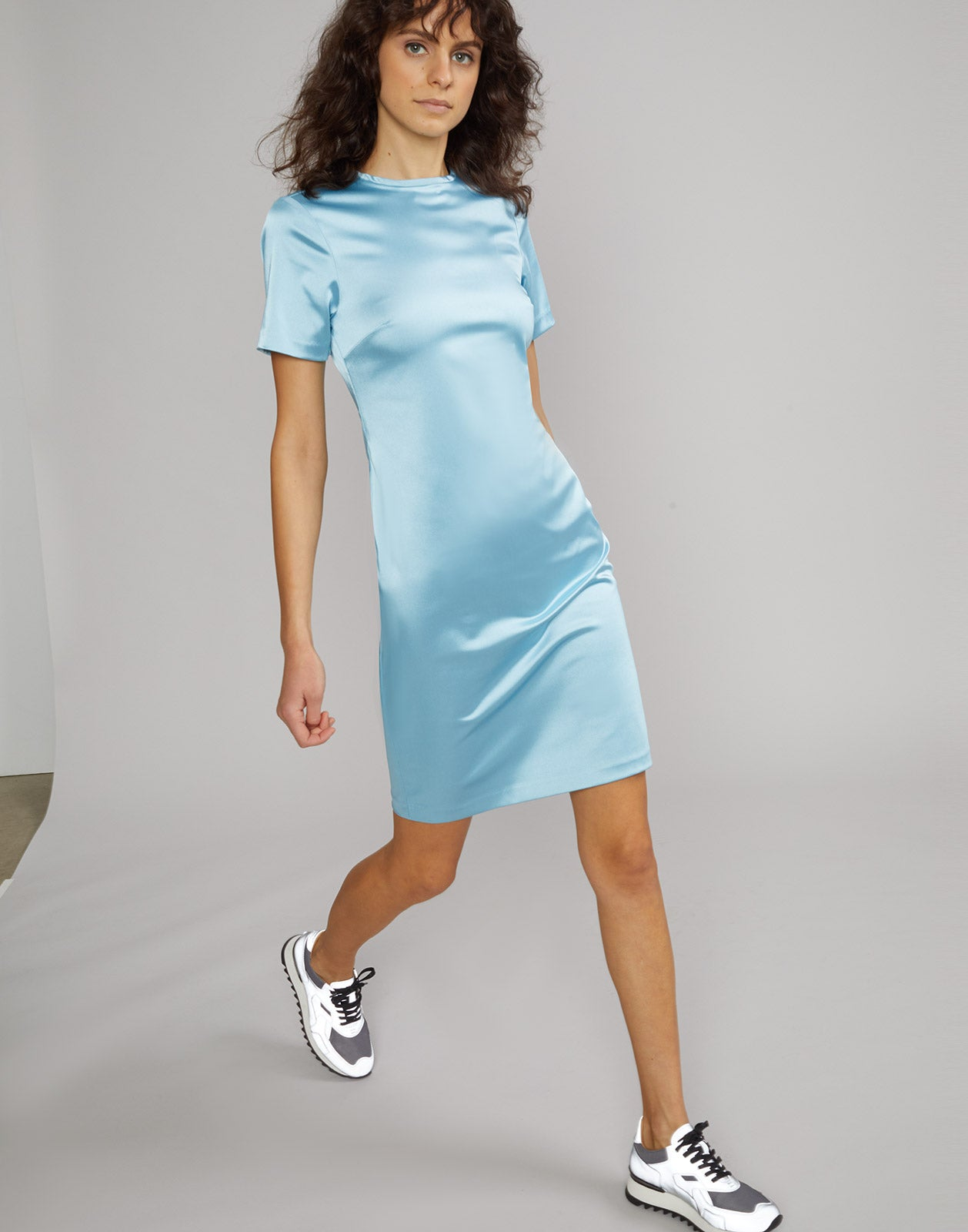 Partial side view of Lake Shore stretch satin t-shirt dress on model.
