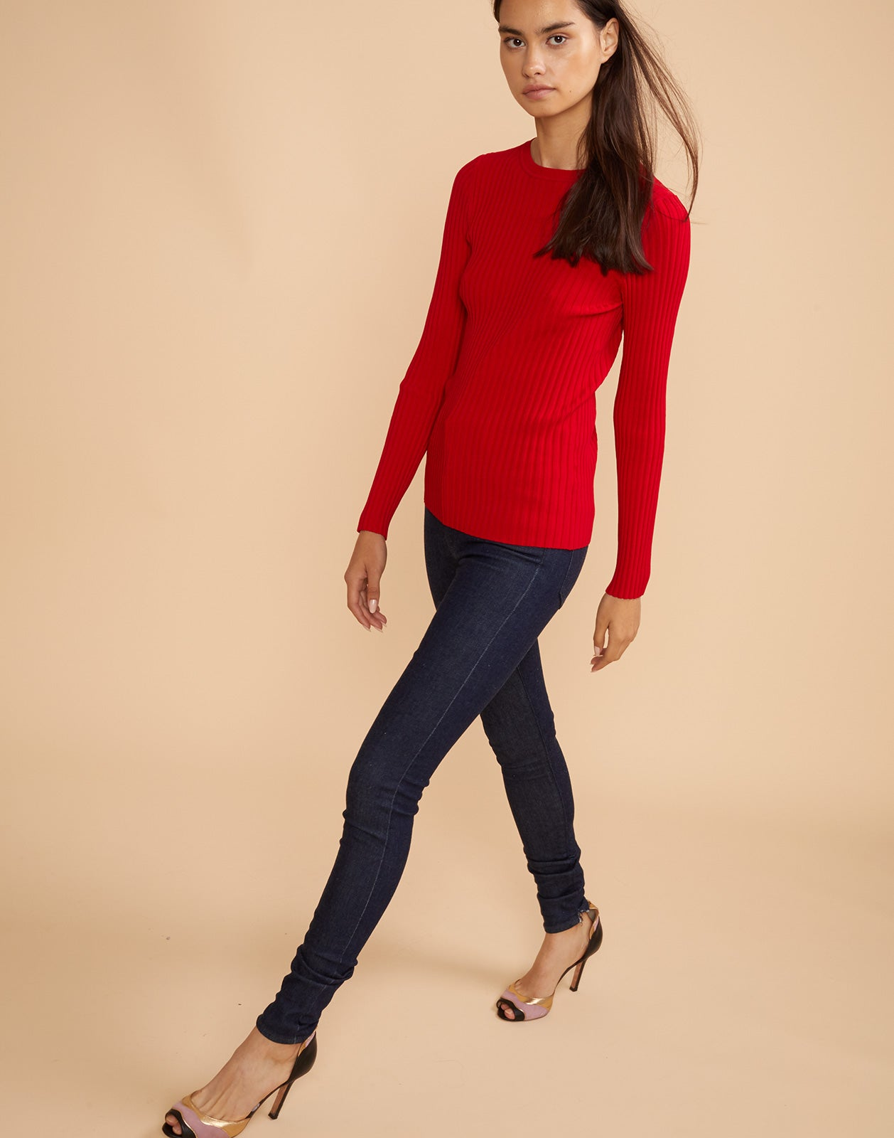 Front view of model walking in Haven ribbed sweater in red.