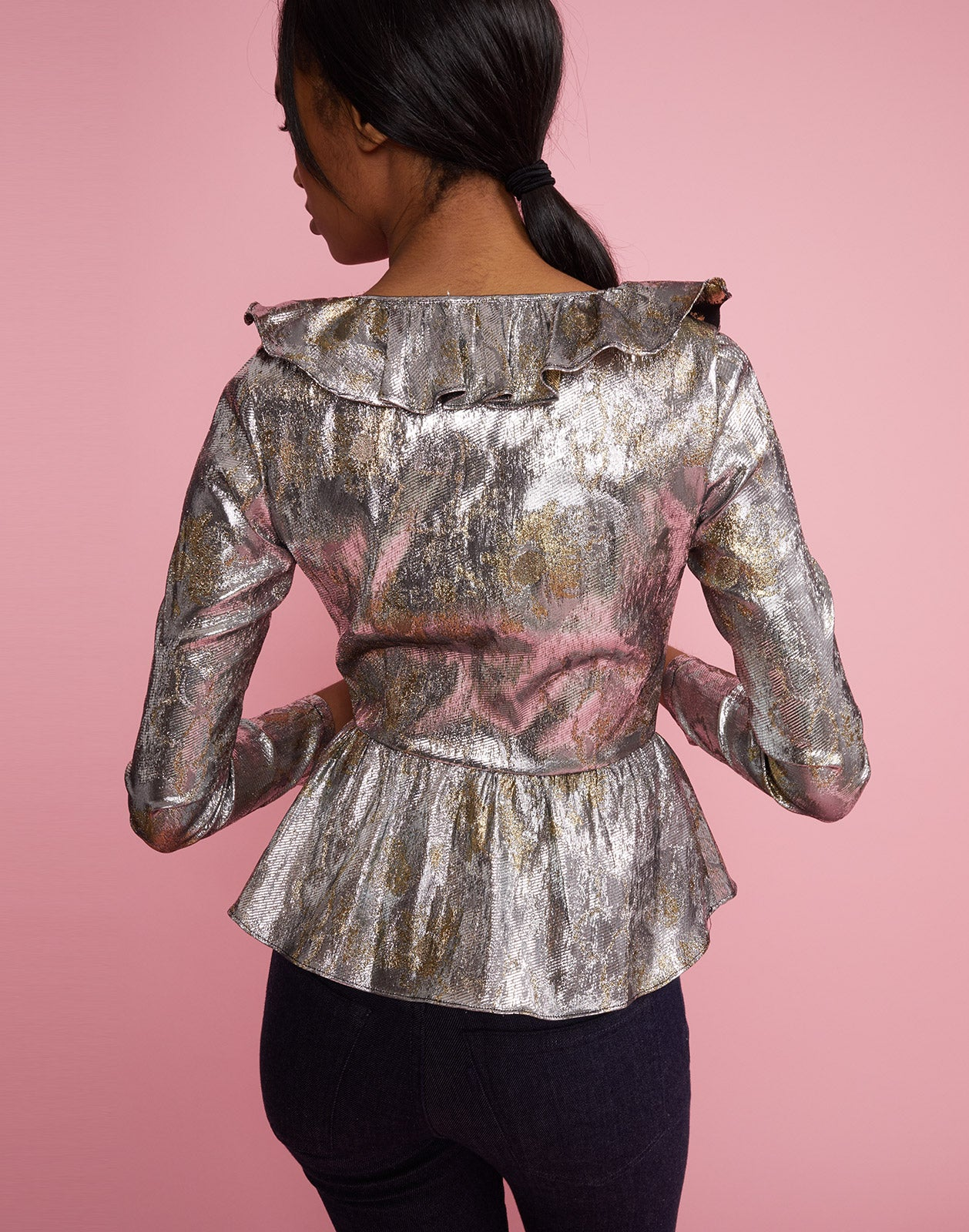 Back view of model wearing Gold Coast Metallic Brocade Ruffle Top.