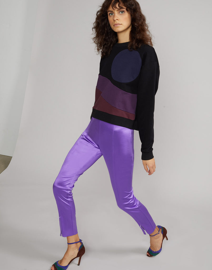 Side view of model wearing ultraviolet Rush stretch satin pant.