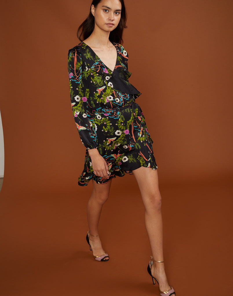 Front view of model walking in vibrant dark floral wrap dress with waist tie.
