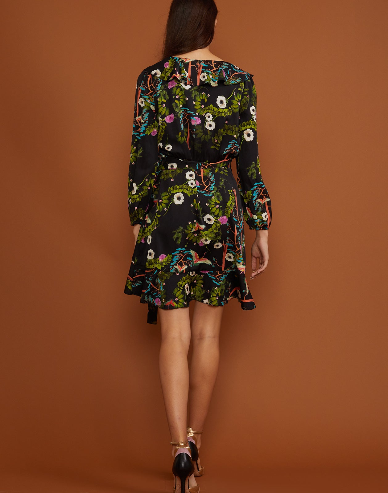 Back view of the vibrant dark floral wrap dress with waist tie.