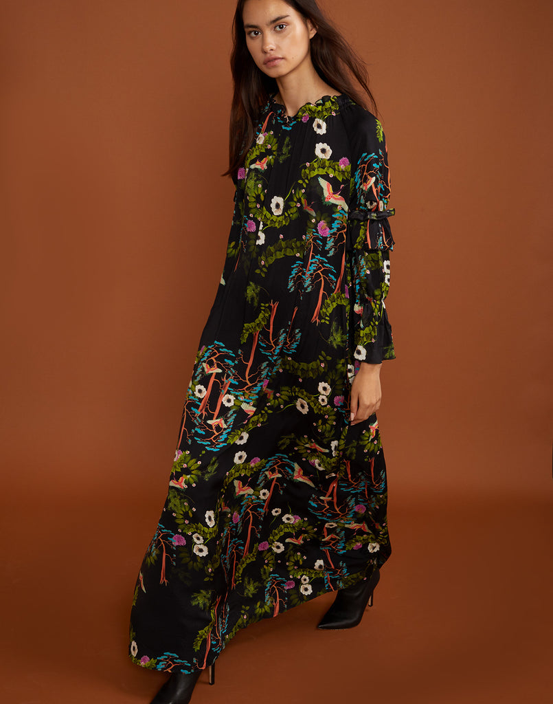 Model walking in the Allegra maxi dress in dark floral print.