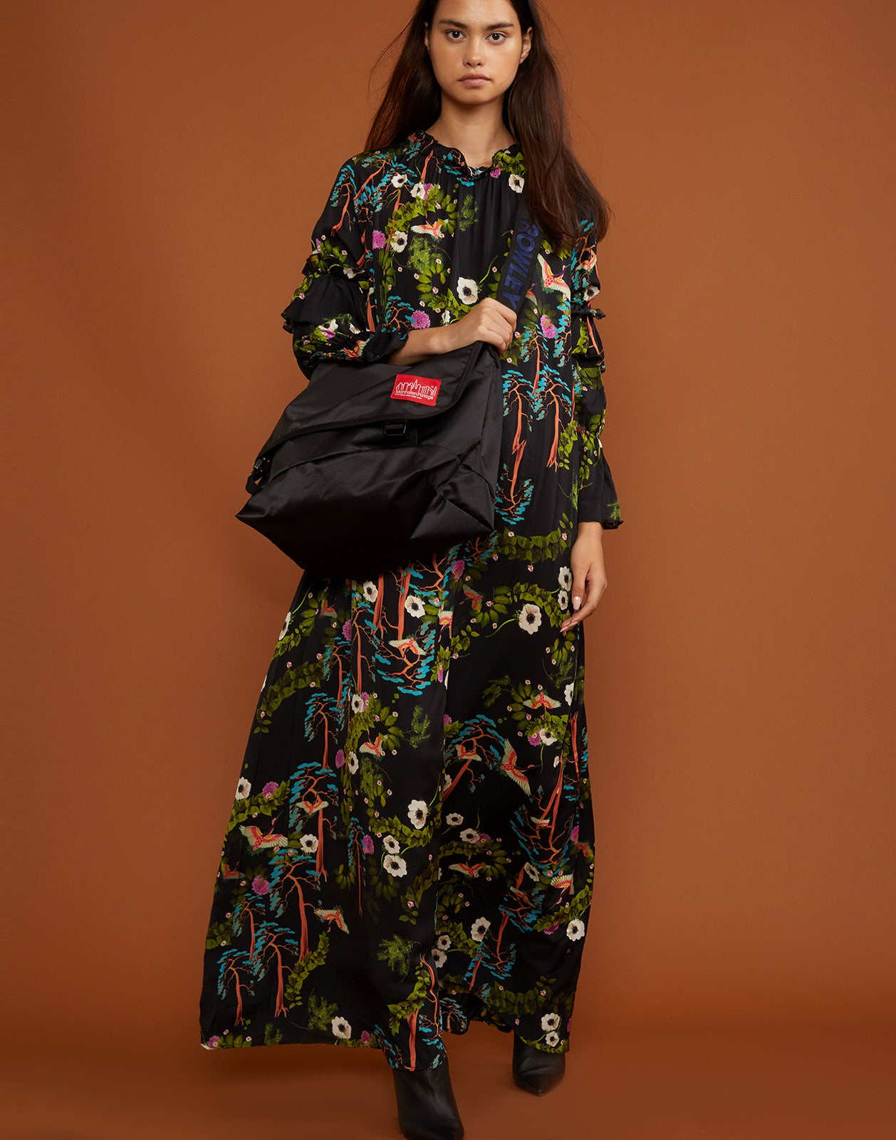 Front view of model wearing the Allegra maxi dress and carrying the large black satin Rowley x Manhattan messenger bag.