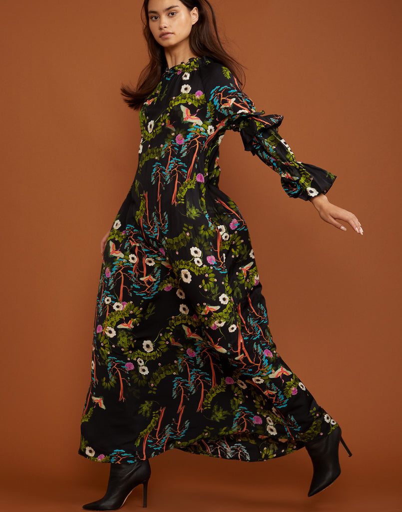 Model jumping through the air in the Allegra dark floral maxi dress.